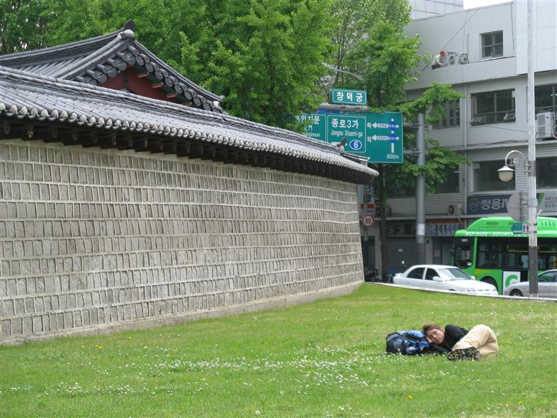 Jen spends the 9 hour layover in Seoul sleeping on the grass