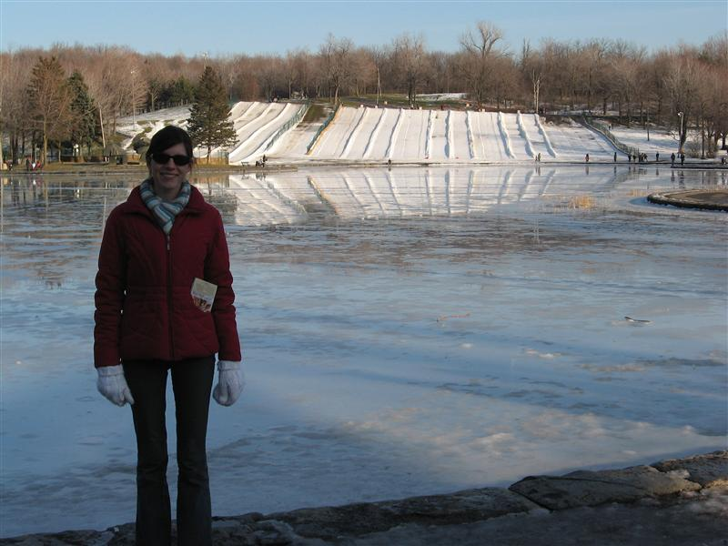 Angela in front of the frozen lake - with the tubing slides in the distance