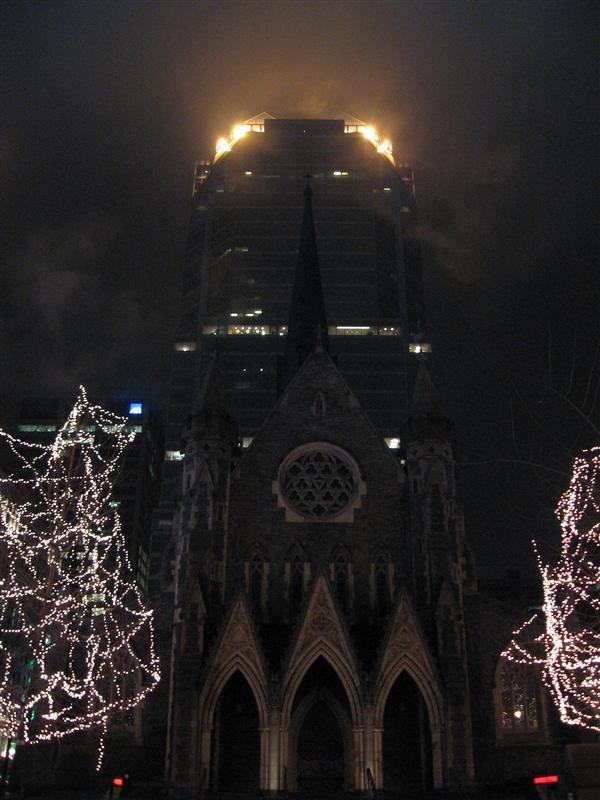A cathedral in front of a spookily-lit skyscraper
