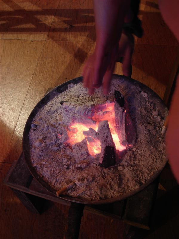 Joanne warms her hands on Coals