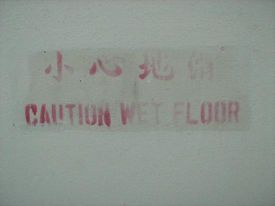 Caution Wet Floor op de muur geschilderd