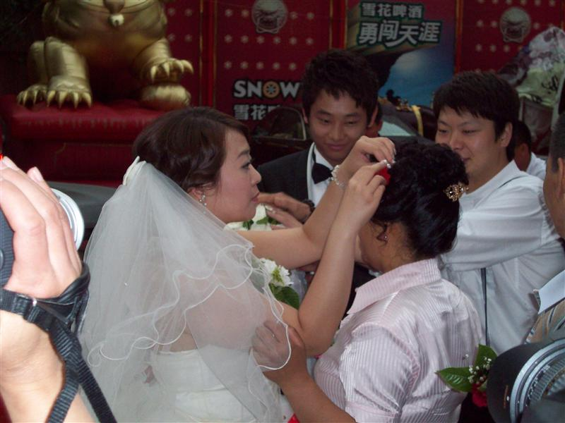 The bride gets out of the car & pins a flower in the ayi's hair