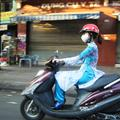 Girl in traditional Vietnamese dress on a moped